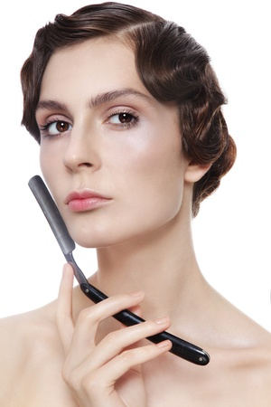 shaver: Beautiful woman with vintage razor in her hand, over white background