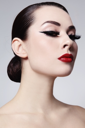 Portrait of young beautiful woman with red lips and cat eyes make-up photo