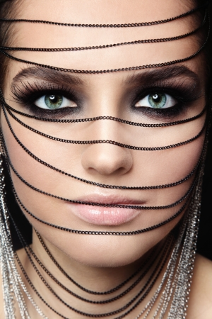 Close-up portrait of young beautiful green-eyed woman with fancy make-up and chains over her face photo