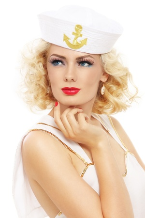 Young beautiful sexy girl with blond curly hair and stylish make-up dressed as sailor, over white background photo