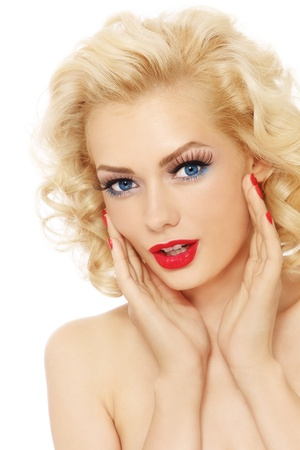 Young beautiful sexy blonde with stylish make-up and hairdo touching her face, over white background photo