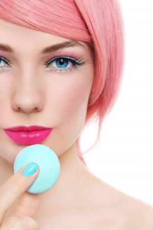guilty pleasure: Primer plano el retrato de una mujer hermosa joven con peluca rosa celebraci�n pastel de macarrones en la mano, sobre fondo blanco