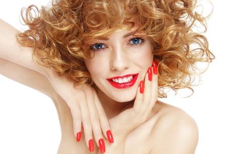 흰색 배경 위에 곱슬 머리와 화려한 매니큐어와 젊은 아름 다운 섹시 웃는 여자