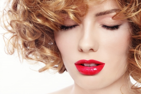 perming: Close-up portrait of young beautiful woman with curly hair and red lipstick