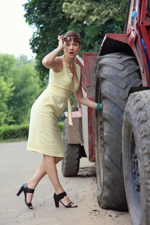 Outdoor humorous shot of slim attractive young woman with shocked expression trying to repair big wheel photo