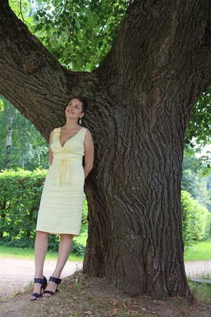 unmarried: Outdoor shot of attractive slim happy smiling young woman in yellow dress under the tree Stock Photo
