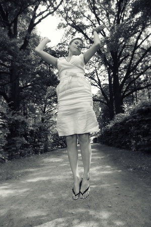 hopping: Outdoor duotone shote of emotional slim young woman hopping happily in the park Stock Photo