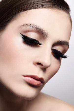 Close-up portrait of young beautiful woman with eyeliner and fake eyelashes photo