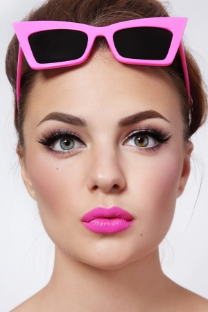 Portrait of young beautiful woman with pink lipstick and stylish vintage sunglasses photo