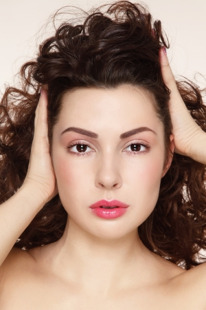 permanent wave: Young beautiful woman with clean make-up touching her long curly hair