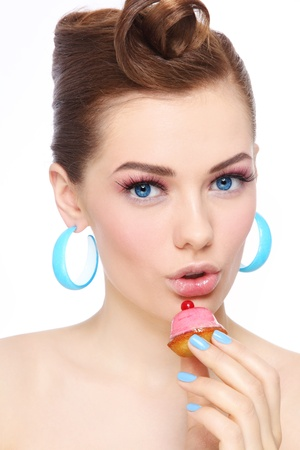 woman eating cake: Portrait of young beautiful woman with petit four pastry in her hand Stock Photo