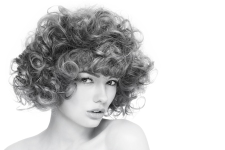 permanent wave: Black and white portrait of young beautiful sexy woman with curly hair over white background