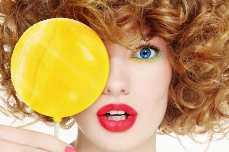 밝은 메이크업과 큰 노란색 막대 사탕을 가진 젊은 아름 다운 여자의 근접 초상화