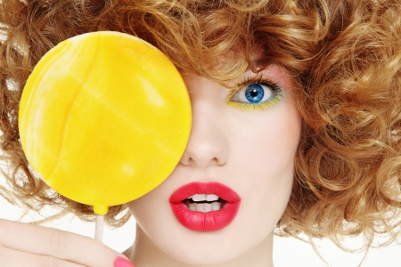 Close-up portrait of young beautiful woman with bright make-up and big yellow lollipop photo