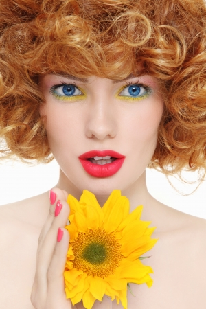 perming: Portrait of young beautiful girl with curly hair and sunflower in her hands