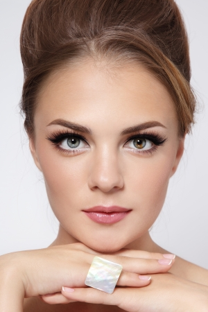Portrait of young beautiful stylish girl with hair bun and trendy make-up