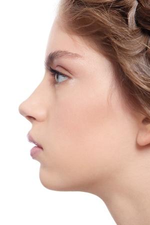 nariz: Retrato de perfil de mujer joven hermosa con maquillaje claro, sobre fondo blanco Foto de archivo