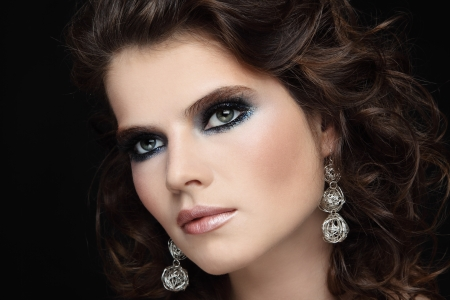 perming: Portrait of young beautiful woman with stylish sparkly make-up and long curly hair