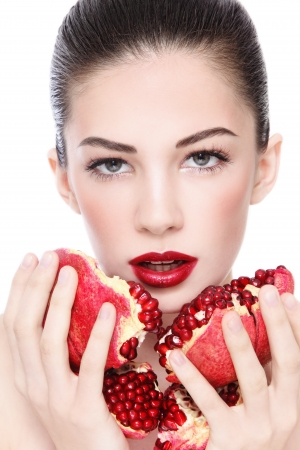 Portrait of young beautiful woman with pomegranates in her hands, over white background photo