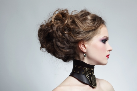 Portrait of young beautiful girl with stylish hairdo and fancy steampunk collar photo