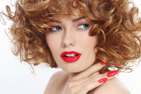 perming: Close-up portrait of young beautiful woman with stylish manicure and red lipstick
