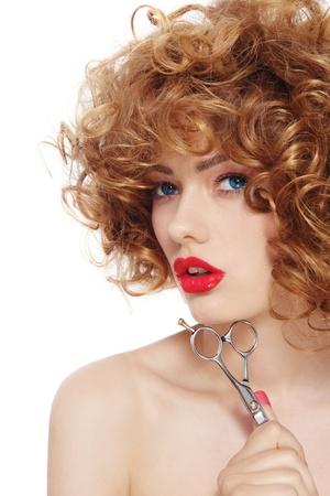 cabello rizado: Retrato de mujer joven y hermosa con el pelo rizado y unas tijeras en la mano, sobre fondo blanco