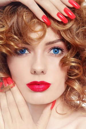 Close-up portrait of young beautiful woman with stylish manicure and red lipstick photo