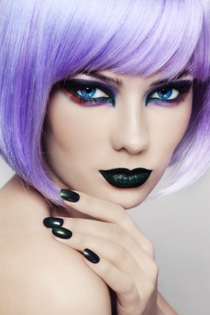 Close-up portrait of young beautiful woman with colorful fancy make-up and violet wig photo