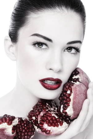 ageing: Duotone portrait of young beautiful woman with pomegranates in her hands, on white background Stock Photo