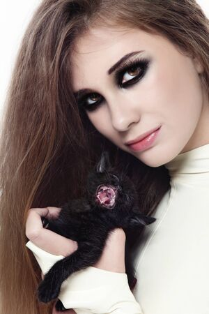 animal ritual: Portrait of young beautiful girl in latex catsuit with smokey eyes makeup and black kitten in her hands
