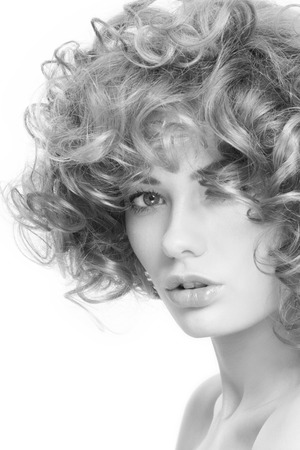 permanent wave: Black and white portrait of young beautiful woman with curly hair over white background Stock Photo