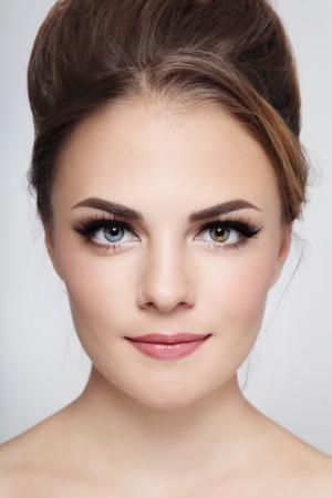 머리 롤빵 및 최신 유행 메이크업 젊은 아름 다운 세련 웃는 소녀의 초상화