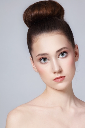 Portrait of young beautiful fresh slim girl with clean make-up and hair bun