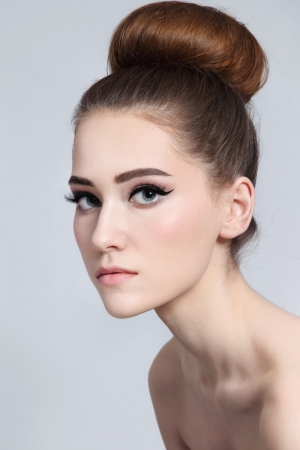 Portrait of young beautiful slim girl with cat eyes make-up and hair bun Reklamní fotografie