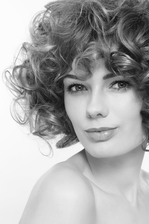 perming: Black and white portrait of young beautiful sexy woman with curly hair