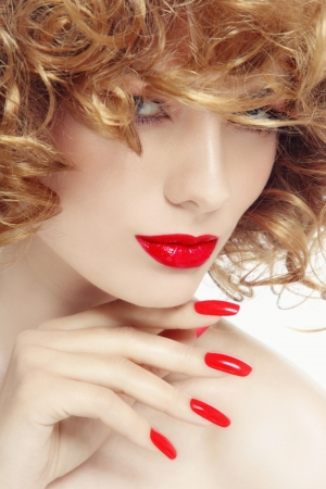 perming: Close-up portrait of young beautiful woman with stylish manicure and red lipstick, selective focus