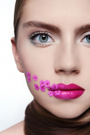 Close-up portrait of young beautiful girl with fuchsia lipstick and small pink flowers on her face photo