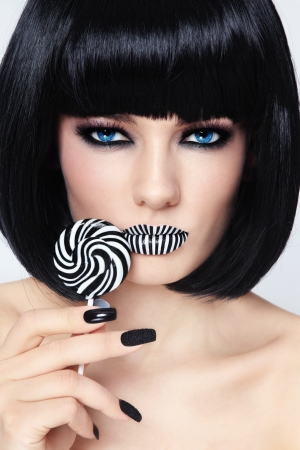 wig: Conceptual portrait of young beautiful blue-eyed brunette with striped lips and lollipop in her hand