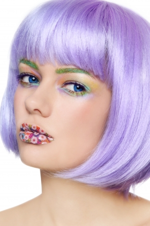 Portrait of young beautiful girl with fancy painted lips and violet wig over white background photo