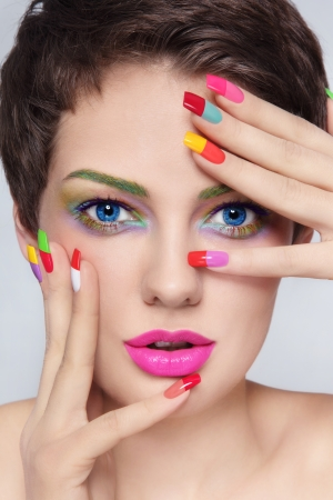 Close-up portrait of young stylish beautiful girl with fancy make-up and colorful french manicure