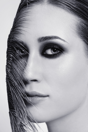 Close-up duotone portrait of young beautiful woman with smokey eyes