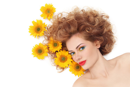perming: Young beautiful healthy woman with curly hair and sunflowers over white background Stock Photo