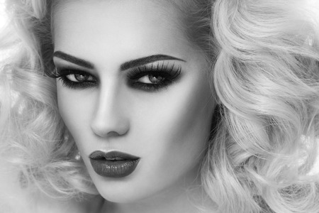 Black and white close-up portrait of young beautiful woman with smoky eyes and blond curly hair