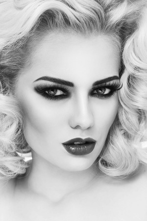 perming: Black and white close-up portrait of young beautiful woman with smoky eyes and blond curly hair