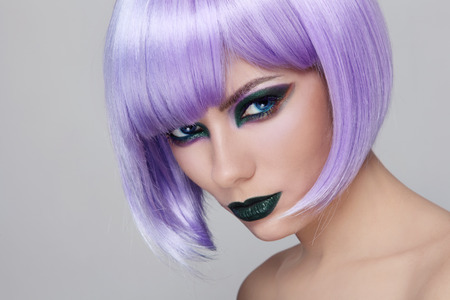 Portrait of young beautiful woman with fancy green make-up and violet wig photo