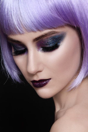 Portrait of young beautiful woman with violet wig and sparkly make-up photo