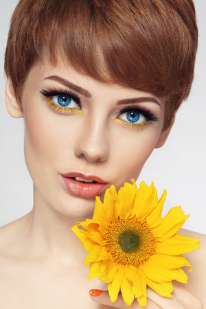 Close-up portrait of young beautiful woman with stylish make-up and sunflower in her hand Stock Photo - 27689997