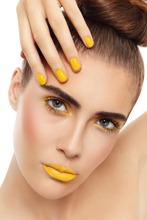 Close-up portrait of young beautiful woman with fancy yellow make-up and manicure over white background photo