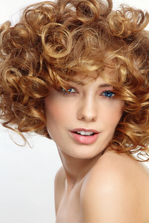 perming: Portrait of young beautiful sexy smiling woman with curly hair Stock Photo