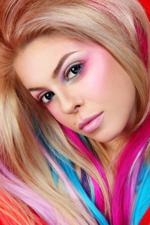 Portrait of young beautiful girl with colorful hair extensions and fancy make-up